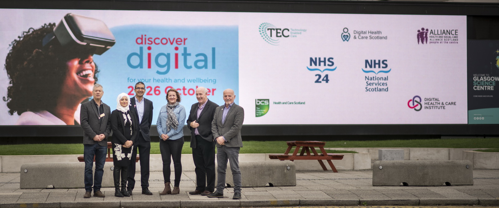 Image of partners standing in front of Science Centre sccreen with discover Digital branding