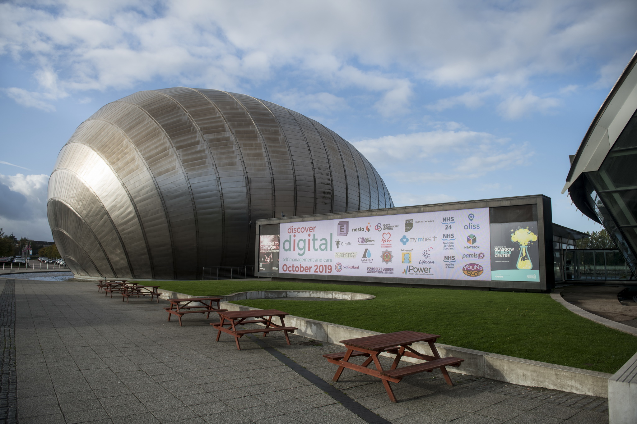 Image of Glagow Science Centre with large screen filled with logos of organisations involved in Discover Digital. Blue sky and green grass fame the picture.