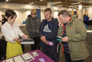 Picture of ClickGo representative presenting the service on a tablet to two onlookers