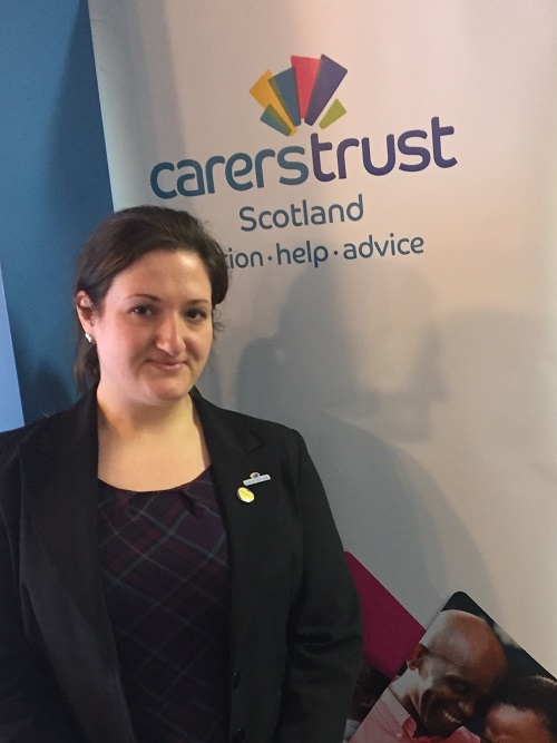 Picture of Heather standing in front of a Carers Trust Scotland banner