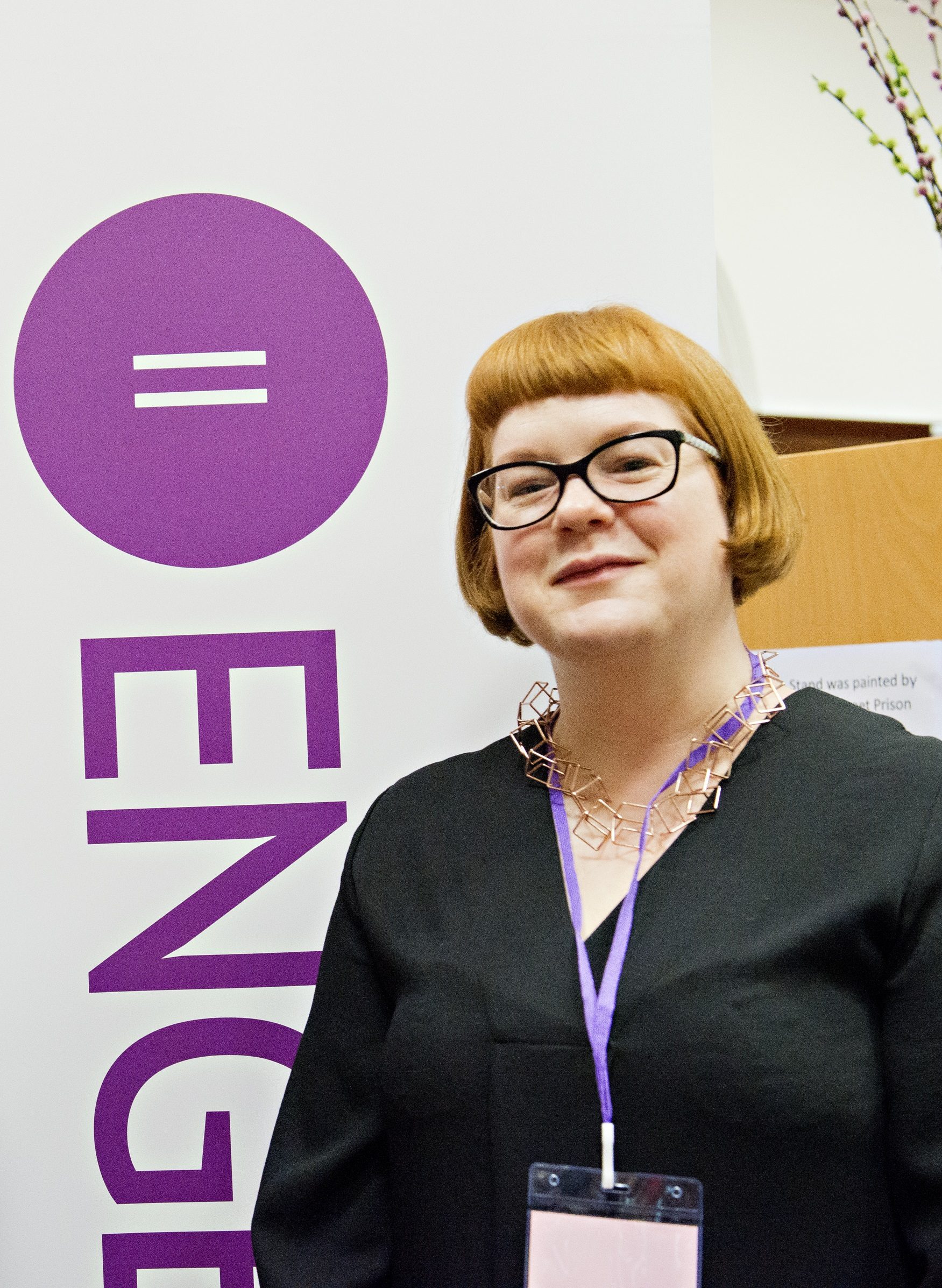 Image of Emma Ritch wearing glasses standing in front of a pop up banner with the Engender logo.