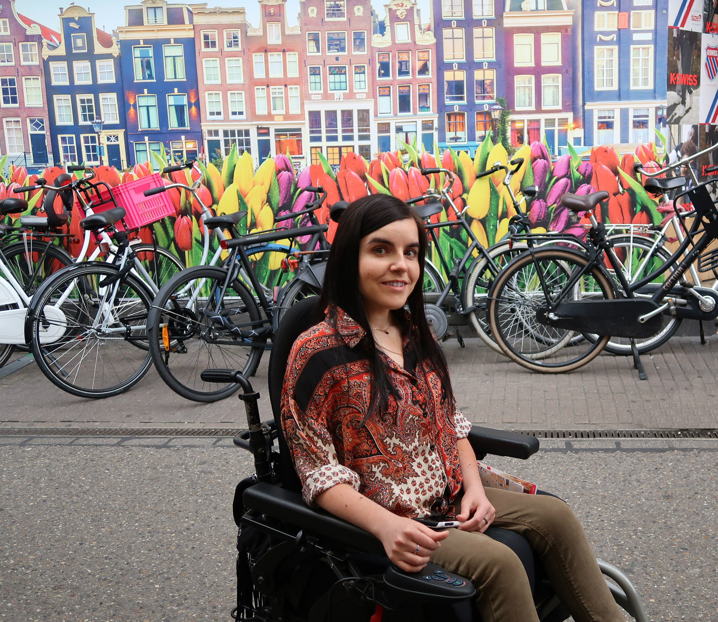 Girl sitting in wheelchair in front of wall with flowers