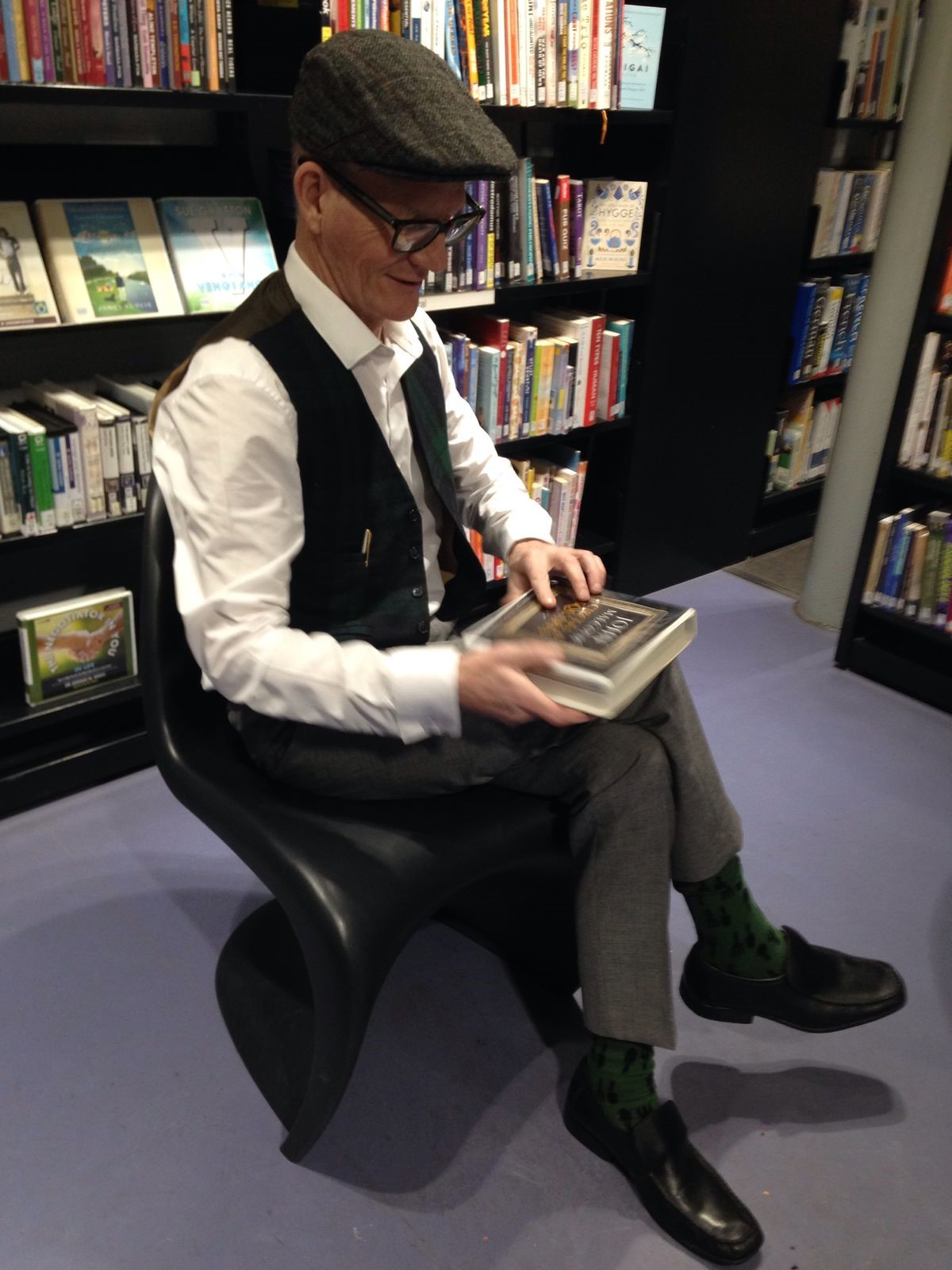 Photo of man sitting in library reading book