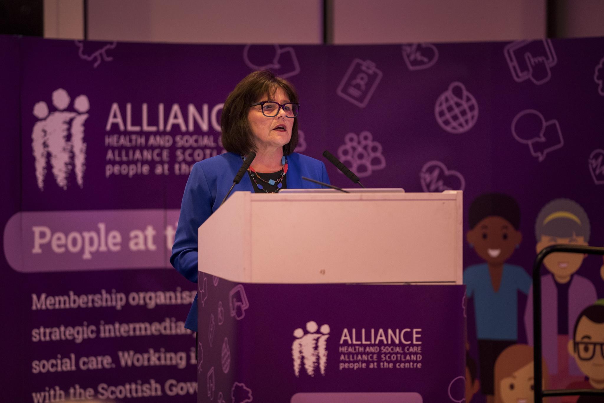 Photo of Cabinet Secretary Jeane Freeman standing on stage