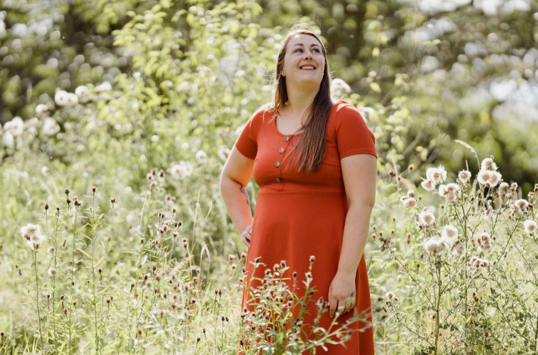 Young woman in orange dress standing in overgrown field area