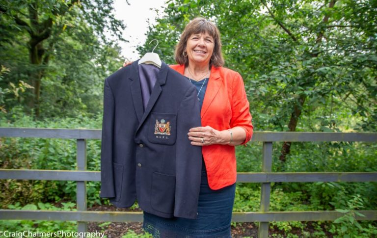 Woman in greenery area holding blazer