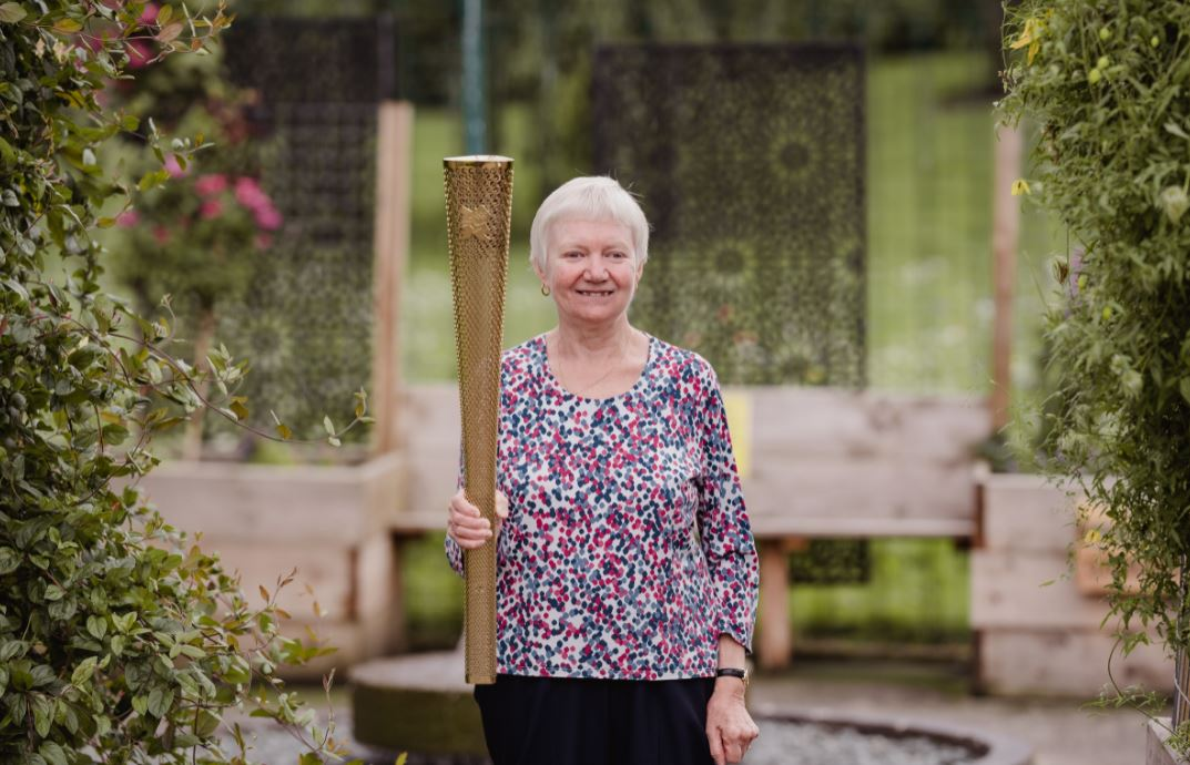 Woman standing in garden with Olympic torch