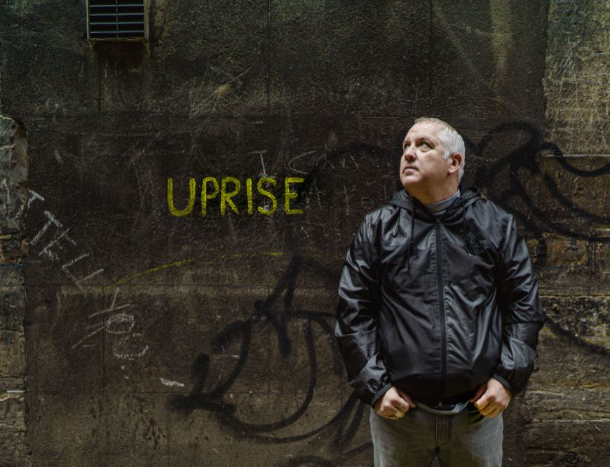 Man standing in front of wall with graffiti of 'uprise'