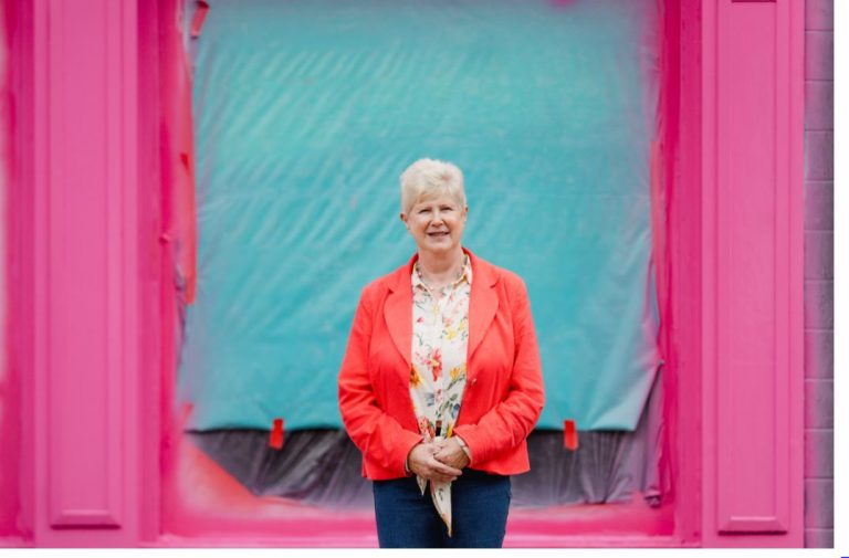 Woman standing in bright pink doorway with blue sheeting in background