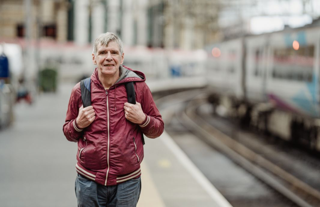 Man standing on train station platform with rucksack on back