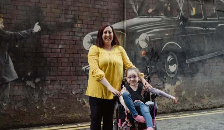 Woman in yellow top with daughter in wheelchair against back drop of graffiti with black taxi backdrop