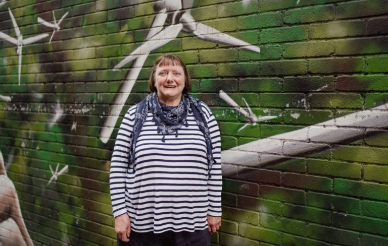 Woman in striped jumper standing against graffiti wall with barbed wire artwork